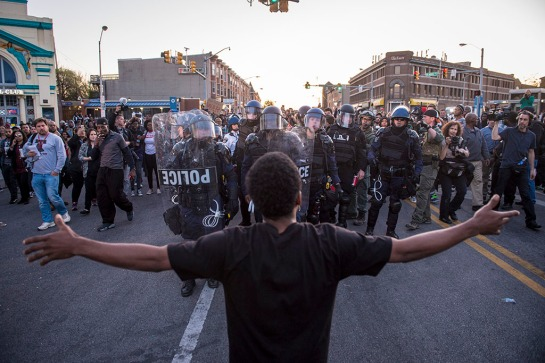 BALTIMORE, MD - APRIL 28: A man stops and yells at officers as they make their way through the crowd to help a person who needed medical attention near the intersection of West North Avenue and Pennsylvania Avenue as protestors walk for Freddie Gray on West North Avenue and protest around the city in Baltimore, MD on Tuesday April 28, 2015. Gray died from spinal injuries about a week after he was arrested and transported in a police van. (Photo by Jabin Botsford/The Washington Post)